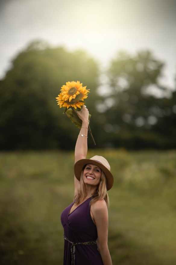 photo of smiling woman holding up bouquet of sunflowers