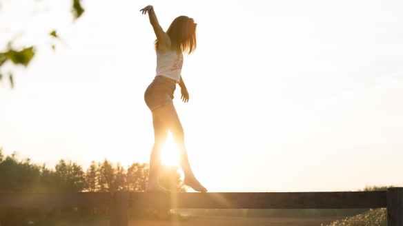 woman walking on fence